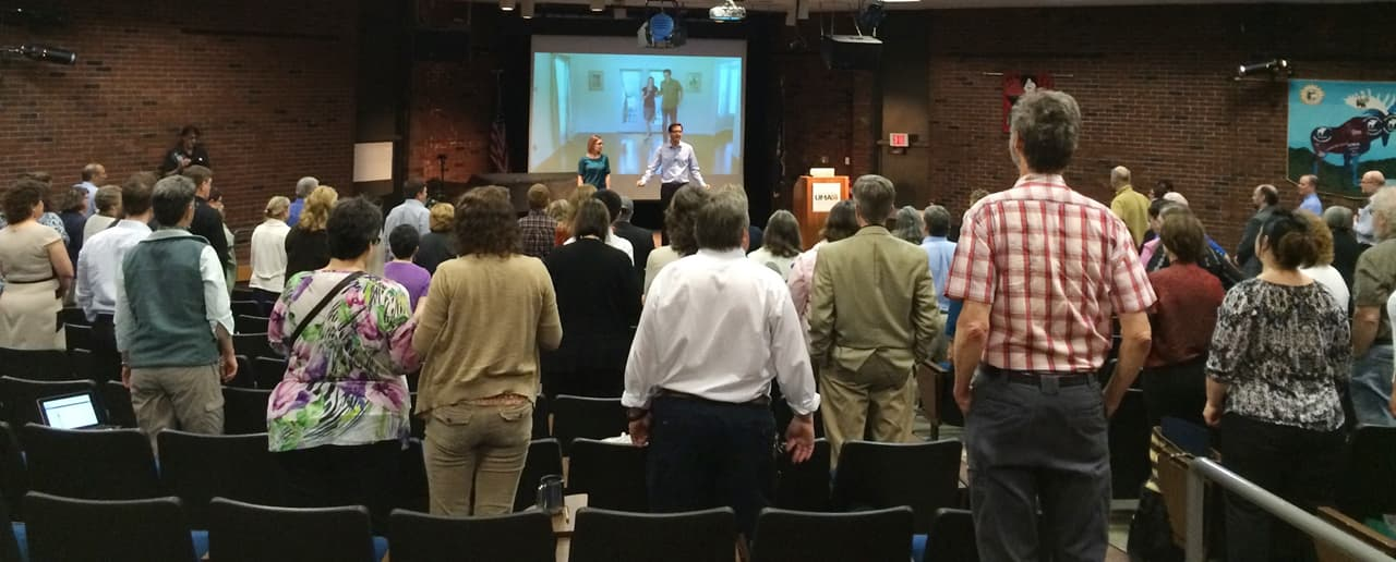 Image of the Faculty Institute Auditorium. Attendees are standing to watch keynote speaker, Lodge McCammon in 2016